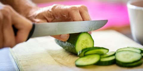 hands of senior woman cutting cucumber on board