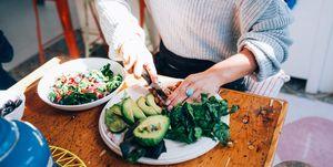 Hands of woman preparing salad