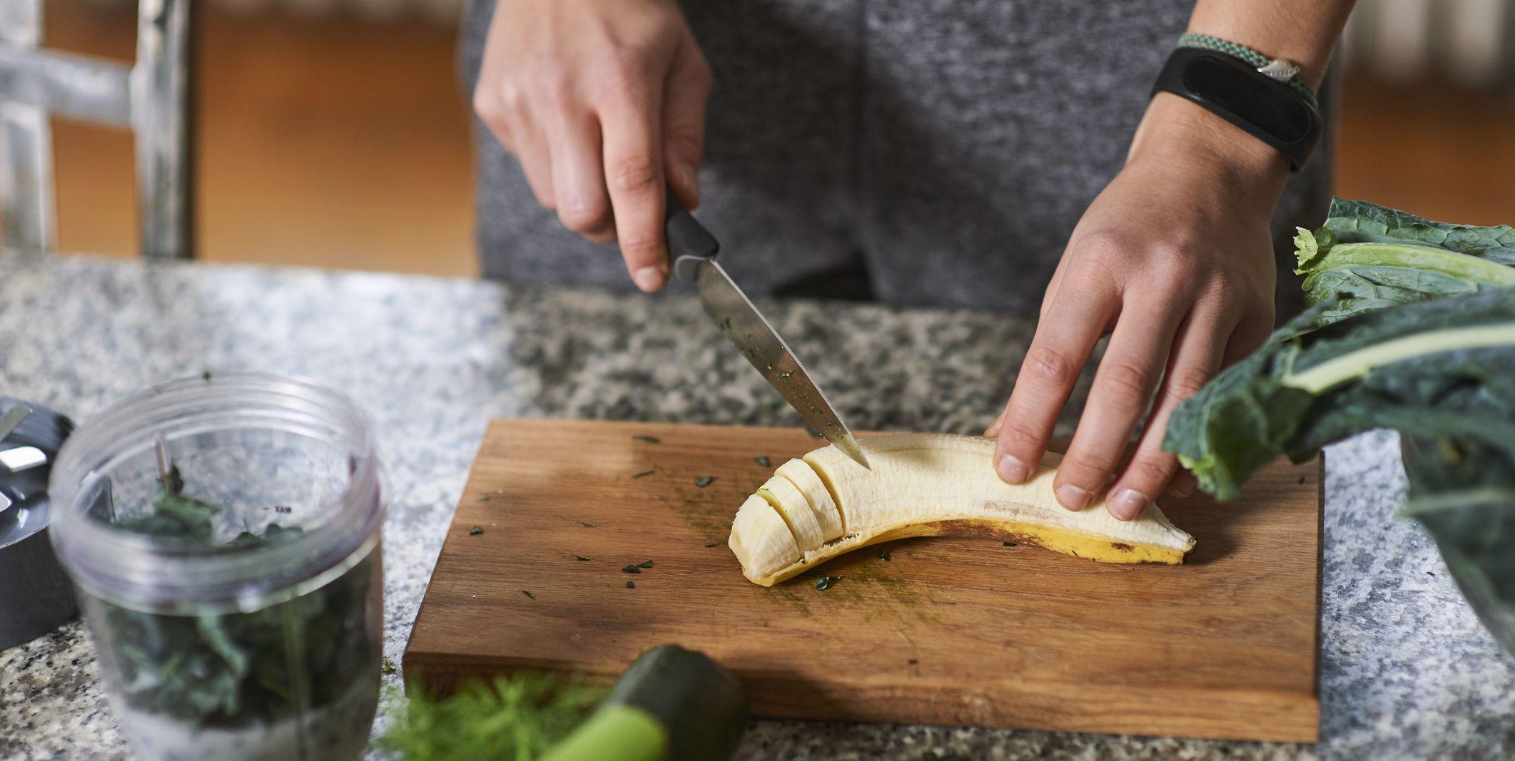 Hands of young woman slicing banana at kitchen table