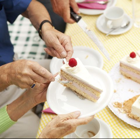 Hands putting cream cake on plates