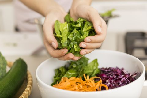 hands putting fresh lettuce into a bowl with different vegetables
