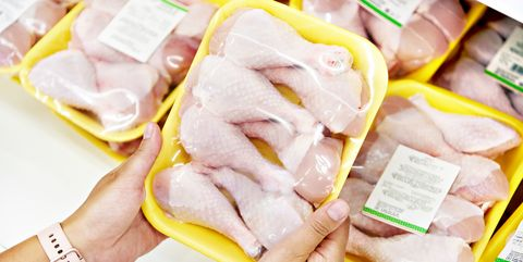 hands with chicken meat in shop