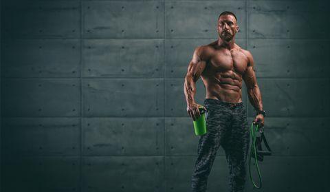Handsome Athletic Men Holding Protein Drink Bottle and Resistance Bands