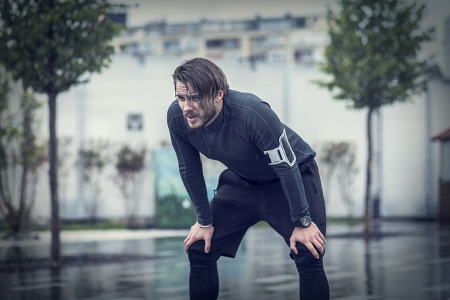 handsome fit man taking a break after workout in the rain