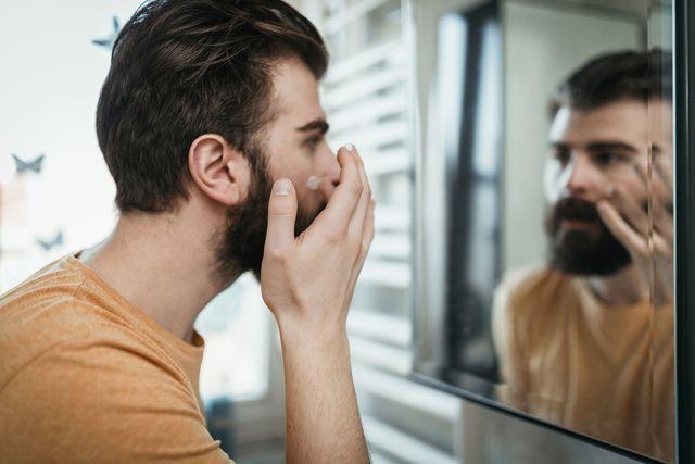 handsome man applying face cream in the bathroom