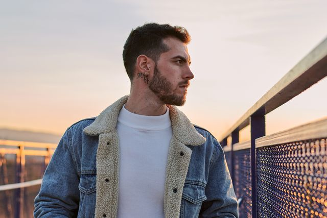 handsome man in a jacket poses on a bridge at sunset