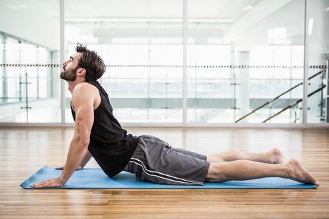 handsome man on cobra pose on the mat
