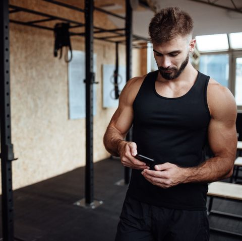 Handsome man using phone in a gym