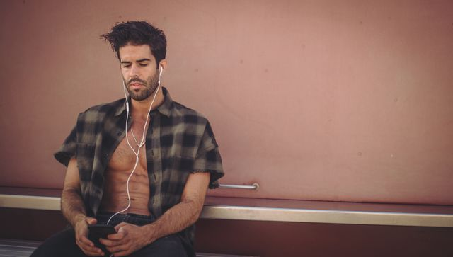 handsome man with headphones sitting outdoors