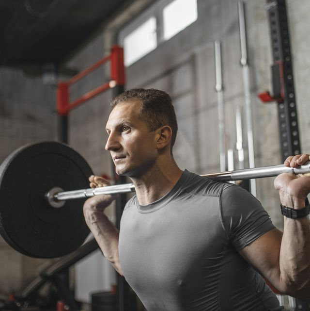 handsome muscular man doing squat exercise with barbell at the gym