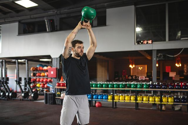 handsome strong athlete doing kettle bell exercises at the gym