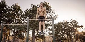 Handsome Young Athlete Doing Chin-ups on Horizontal Bar