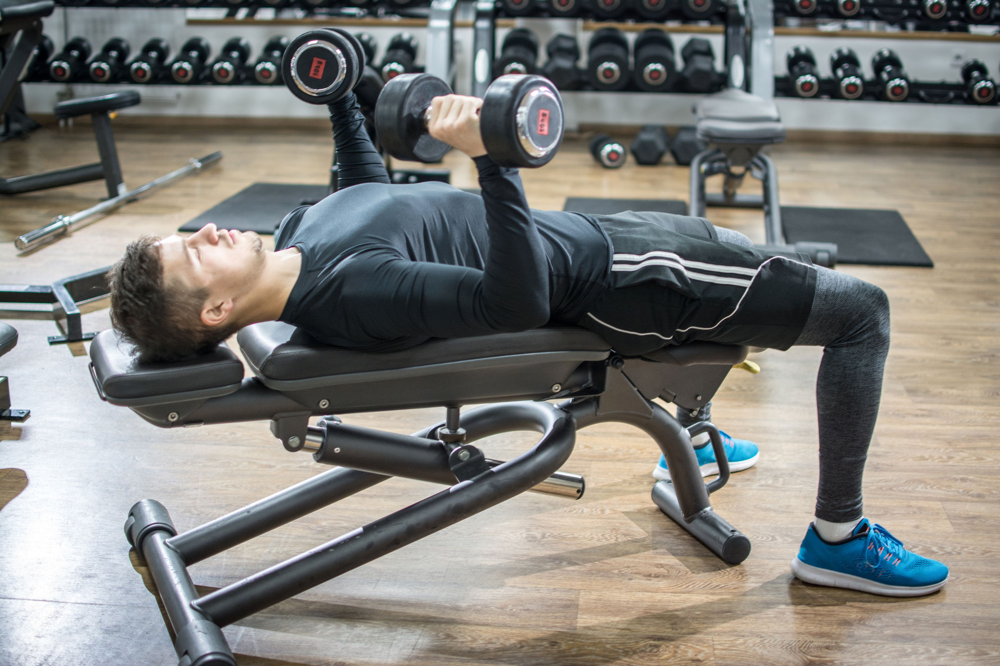 Awesome Handsome Young Man Lying On Exercise Bench And Lifting Dumbbells In Gym
