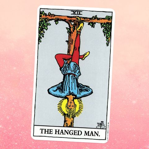 the tarot card the hanged man, showing a man hanging upside down, with one foot tied to a tree