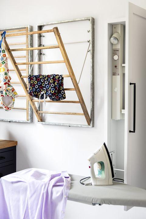 laundry room with drying racks, ironing board designed by emilie munroe, studio munroe