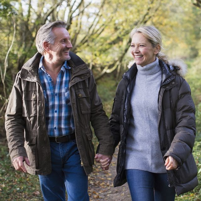 Happy, affectionate mature couple holding hands and walking in autumn park