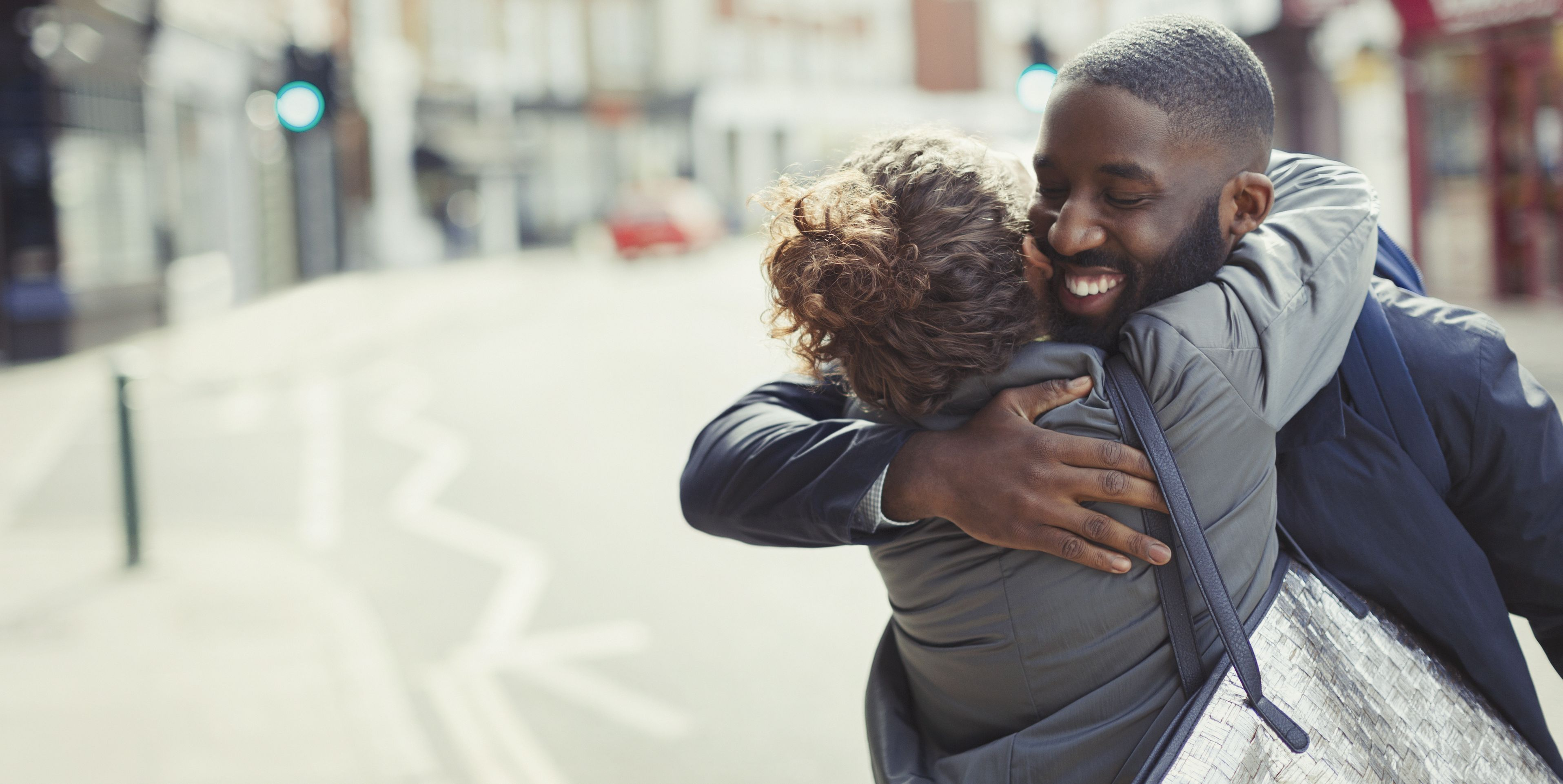 Happy, affectionate young couple hugging on sunny urban street