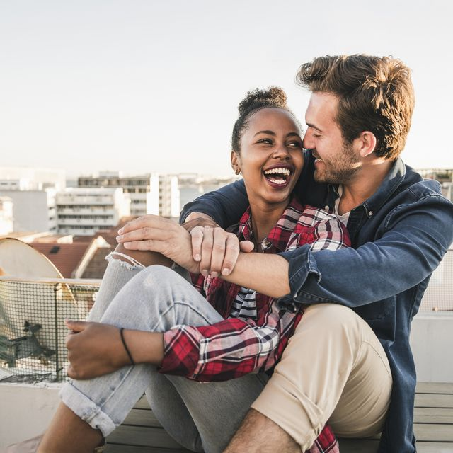 happy affectionate young couple sitting on rooftop in the evening