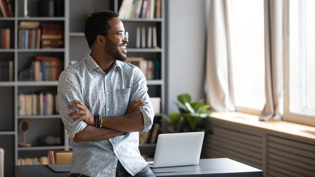 Happy african business man looking away dreaming standing in office