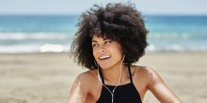 Happy afro american woman listening music on beach looking away
