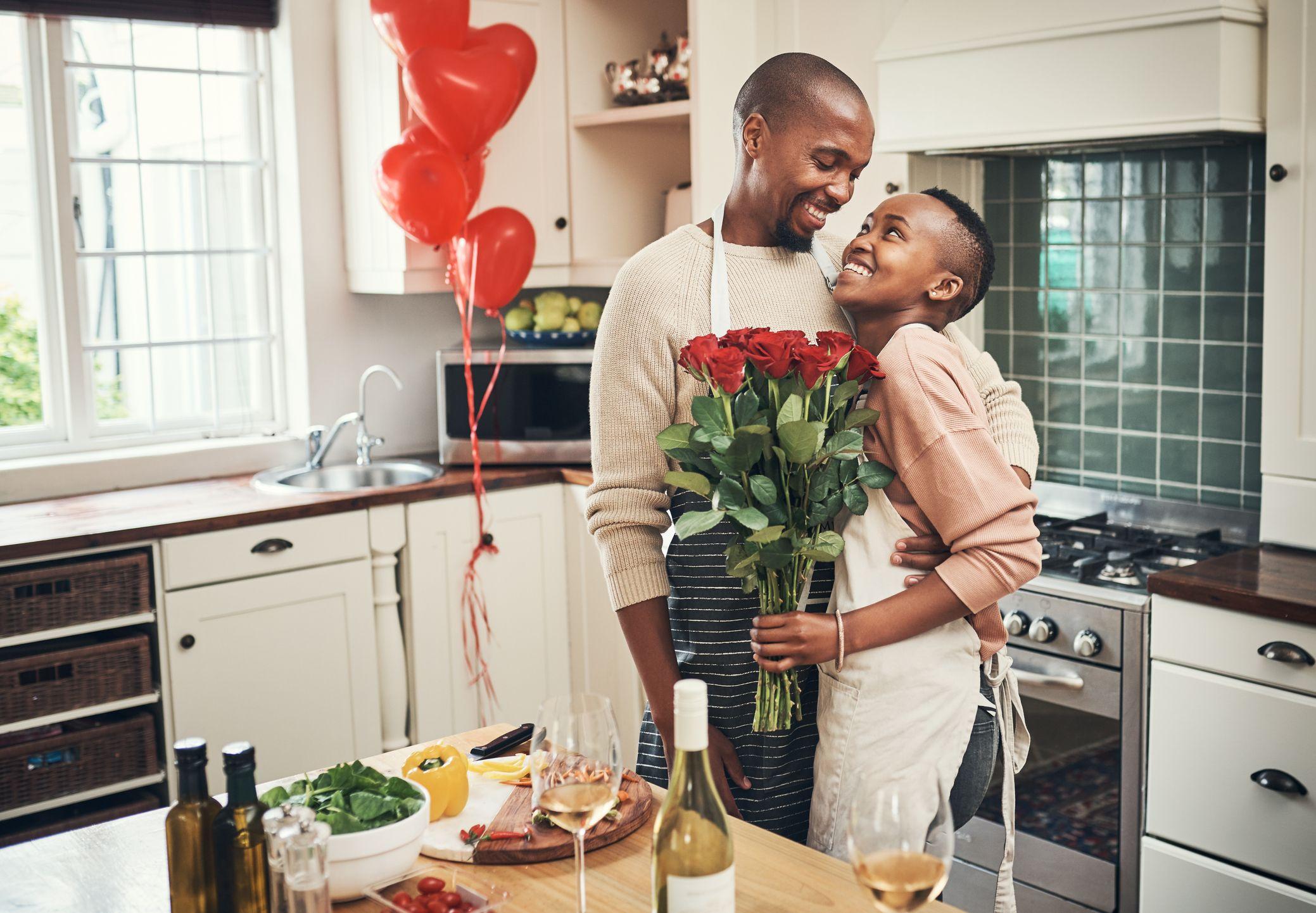 svart par på et kjøkken med røde ballonger, vin og røde roser
