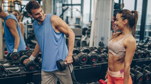 Happy athletic couple talking while taking weights from a rack in a gym.