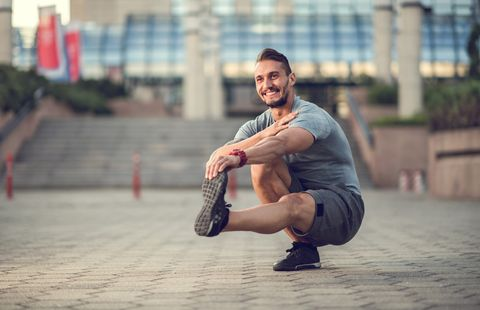 Happy athletic man stretching his leg while crouching outdoors.