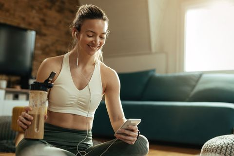 happy athletic woman using mobile phone while drinking smoothie at home