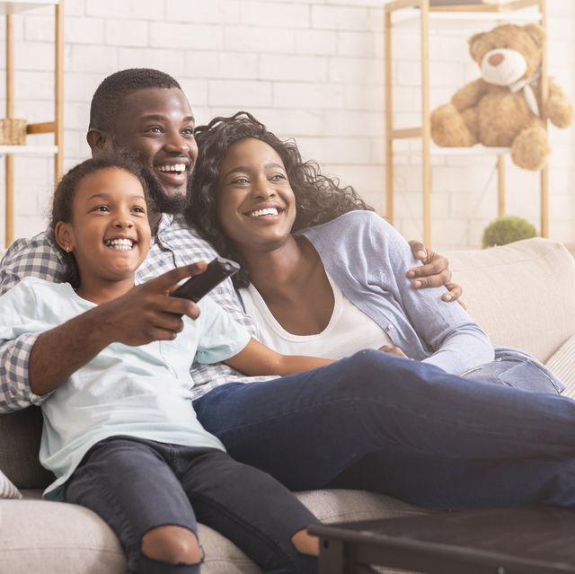 happy family relaxing and watching tv at home
