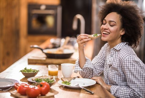 Happy black woman enjoying during breakfast time in the kitchen.