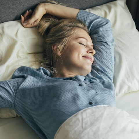 feeling energized happy blonde woman in pyjamas stretches in bed after waking up