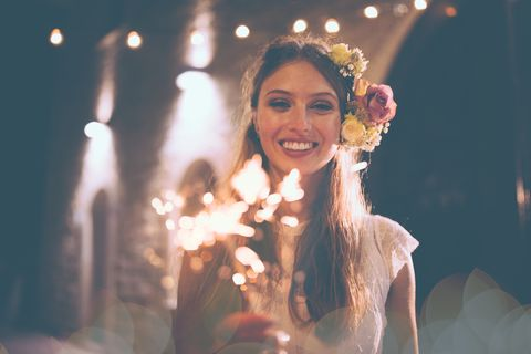 839899e9e0dc Happy bride in white wedding dress holding sparklers and celebrating