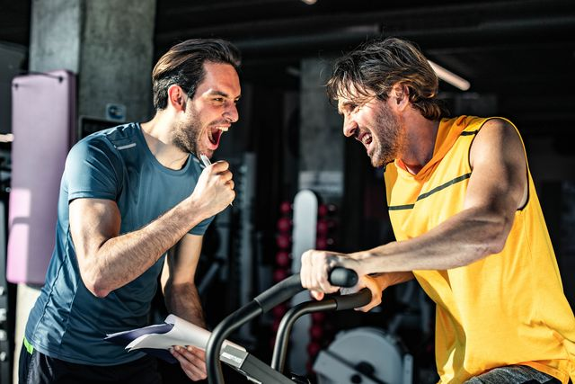 happy coach cheering for athletic man on stationary bike in a gym