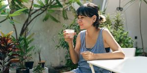 happy confident asian woman drinking smoothie in the garden at home. short highlighted hair