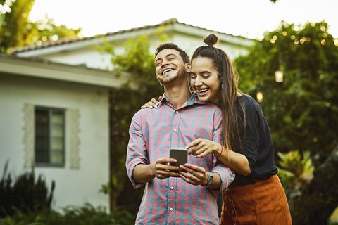 happy couple looking at smart phone in back yard