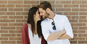 Happy couple standing in front of brick wall, kissing