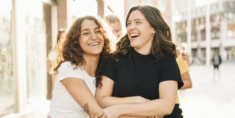 Happy female friends embracing in city during sunny day