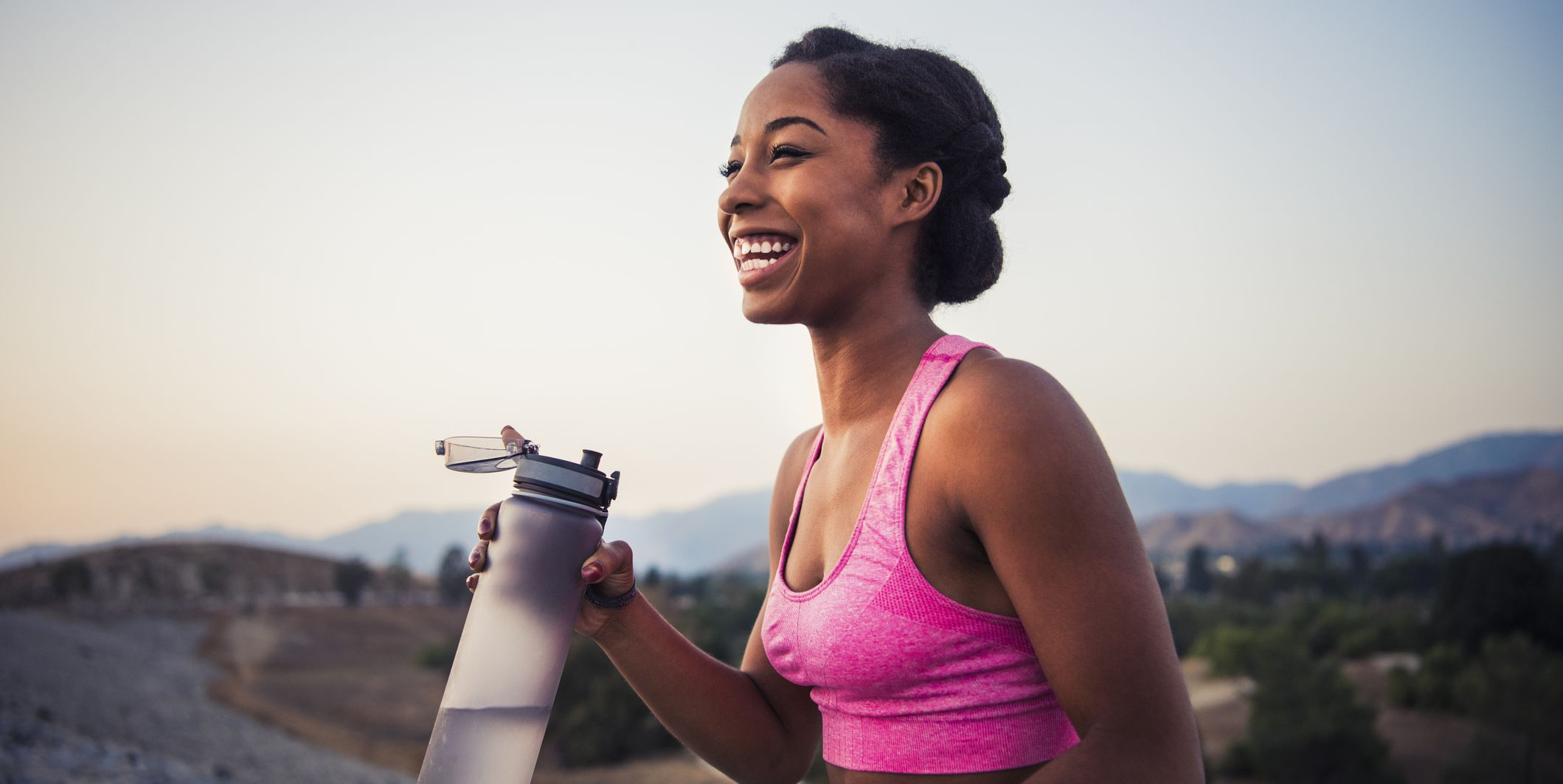 Happy female runner holding water bottle