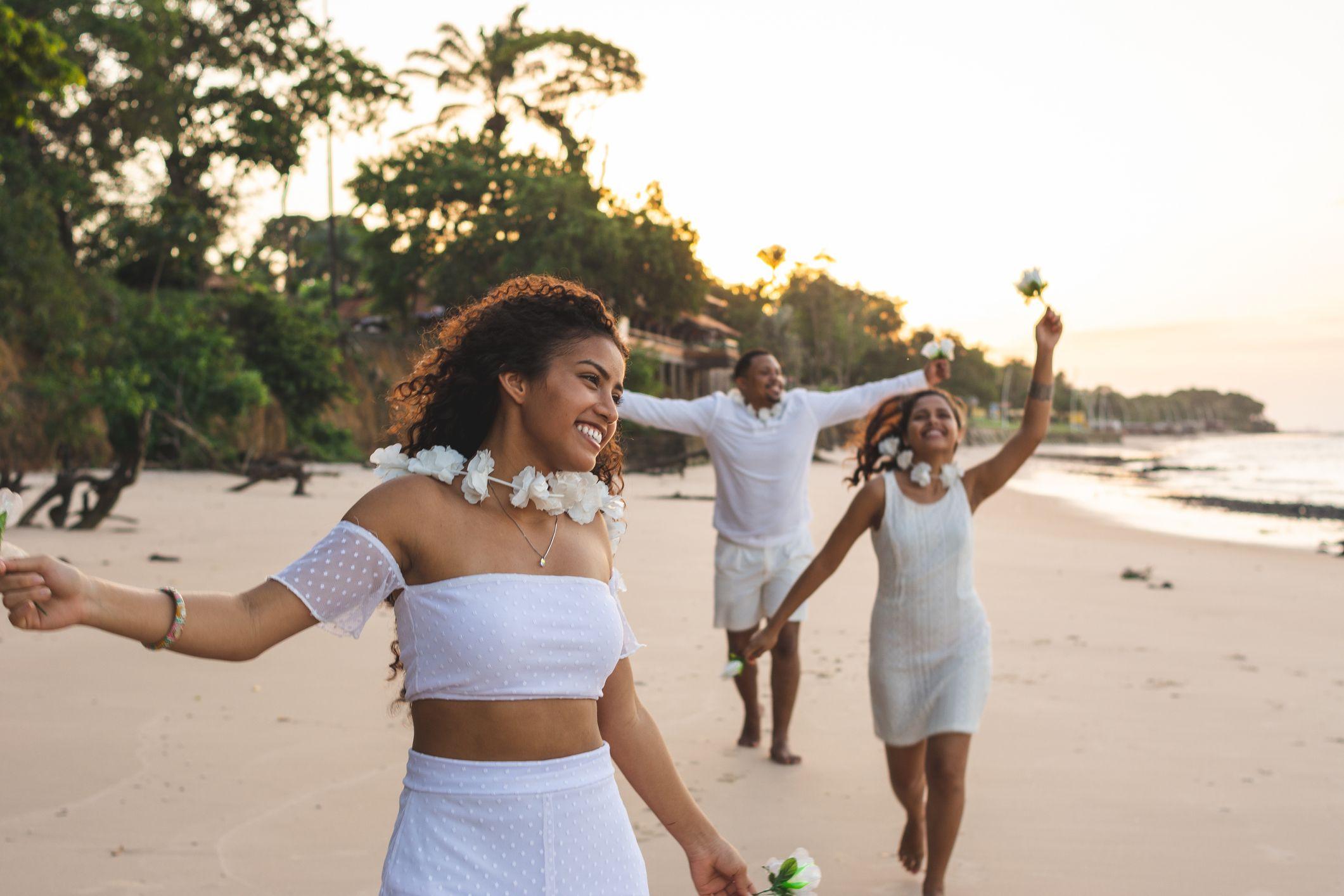 Heureux amis célébrant le réveillon sur la plage, courir et tenant des fleurs blanches paraiso beach, mosqueiro