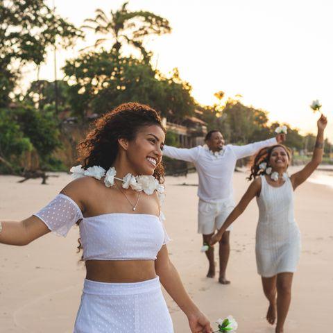 happy friends celebrating reveillon on the beach, running and holding white flowers paraiso beach, mosqueiro