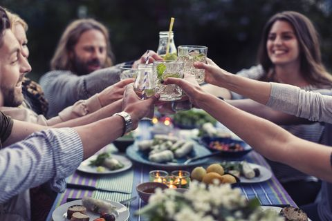 happy friends toasting mojito glasses at dinner table in yard