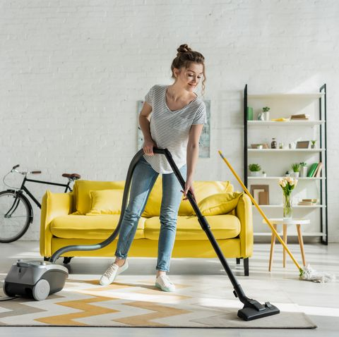 happy girl cleaning carpet with vacuum cleaner