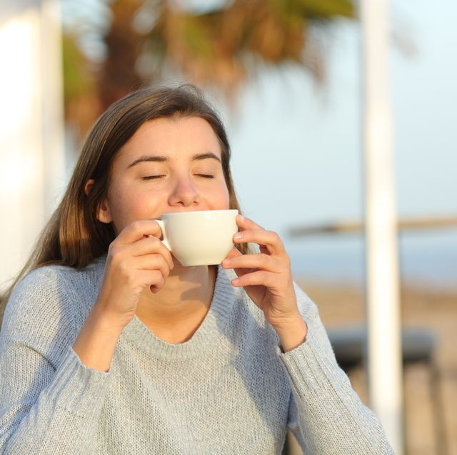 happy girl relaxing smelling coffee aroma in a cafe