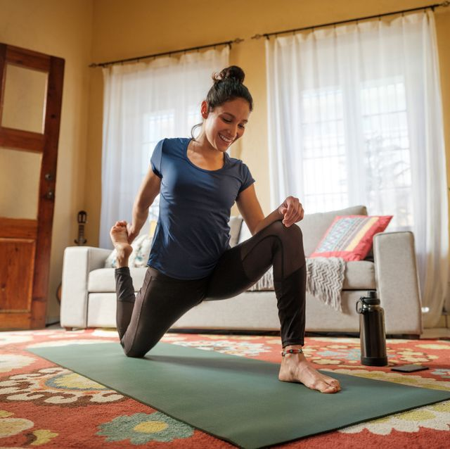 happy latin woman stretching legs on mat in living room