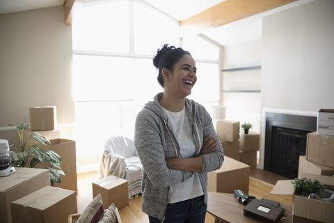 Happy, laughing young woman moving house, surrounded by cardboard boxes