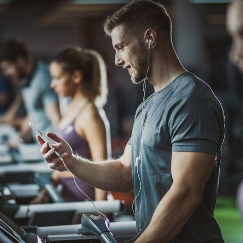 Happy male athlete listening music on treadmill in a gym.