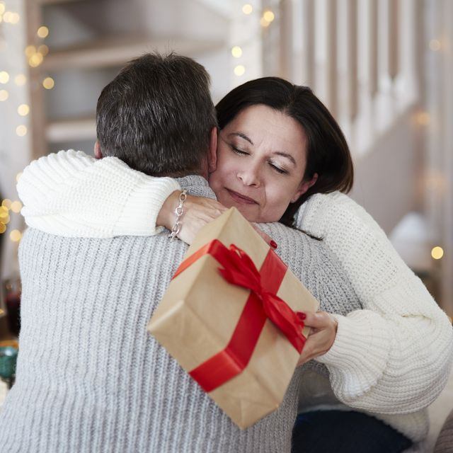 happy mature couple with gift box hugging in living room