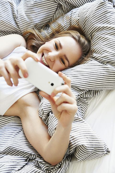 quarantine birthday ideas - happy mid-adult woman laying in bed taking a selfie with her smartphone