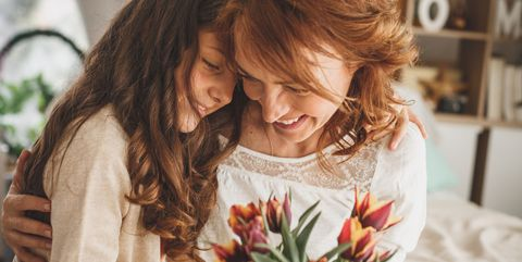 happy mother and daughter hugging and holding a bouquet of fresh flowers