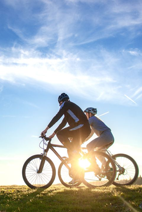 Happy mountain bike couple outdoors have fun together on a summer afternoon sunset